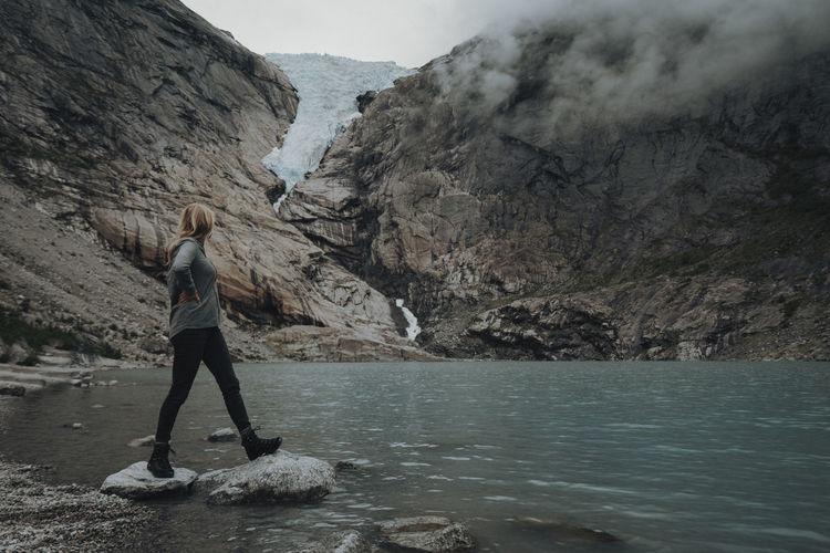 Rear view of woman walking on rock in water