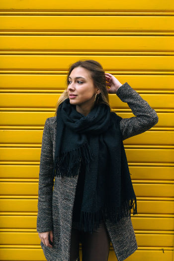 Young woman standing against yellow wall