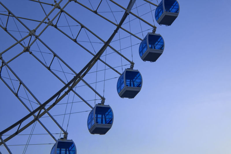 Low angle view of overhead cable car against clear blue sky