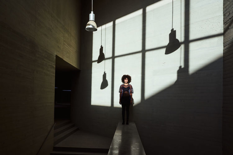 Portrait of woman standing against wall in building