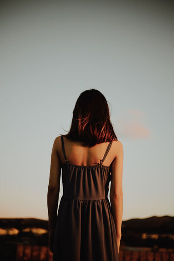 Rear view of young woman standing against clear sky