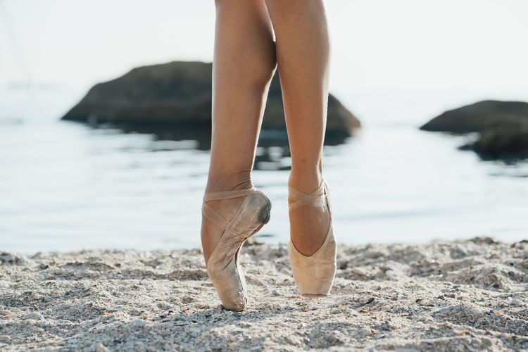 Low section of ballerina dancing at beach