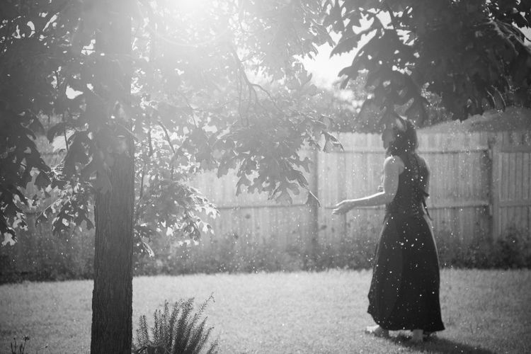 Adult Arms Outstretched Back To Camera Backyard Black And White Day Dress Fence Full Body Grass Monochrome Nature Oak Tree One Person Outdoors Peaceful Person In Nature Poetic Portrait Skirt Sunshine Tree Tree Trunk Walking Woman