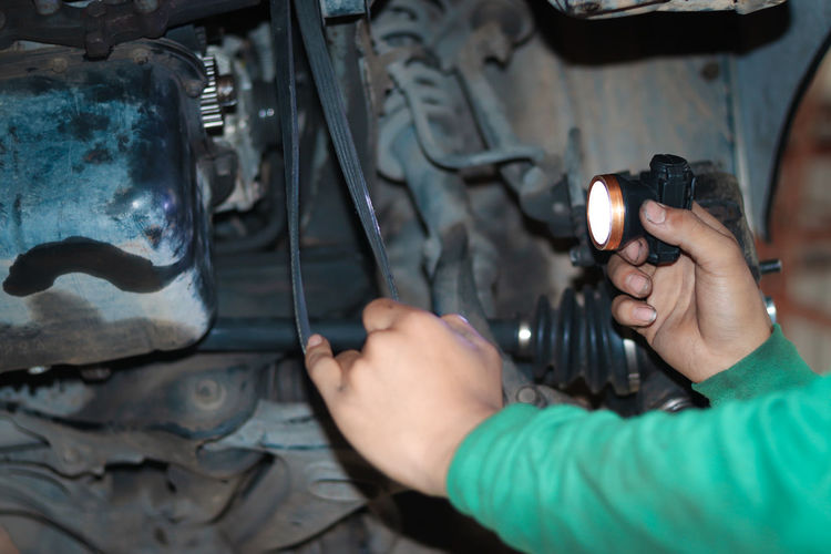 Cropped hand of mechanic repairing vehicle at garage