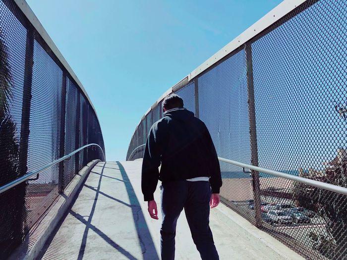 Rear View Of Man Walking On Footbridge