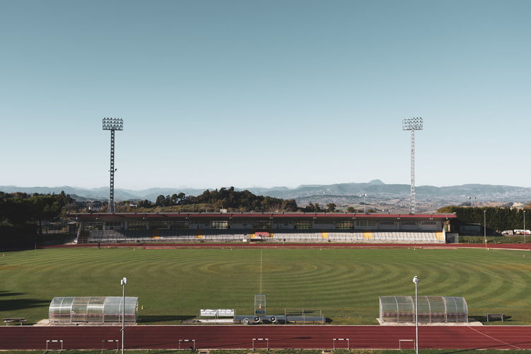 small stadium High Angle View Playing Field Lighting Equipment Plant Outdoors Built Structure Floodlight No People Practice Training Contest Match Poles Dribbling Field Goal Seats Play Football Competition Running Implant Track Grass Small Cement Architecture Pylons Light Bleachers Steps View Landscape Panorama Mountain Range Nature Movement Athletic Soccer Stadium Sport Grandstand