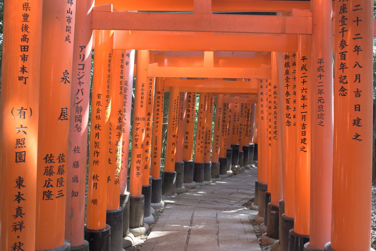 orange color, in a row, shrine, place of worship, religion, spirituality, text, the way forward, travel destinations, architectural column, day, no people, outdoors, architecture