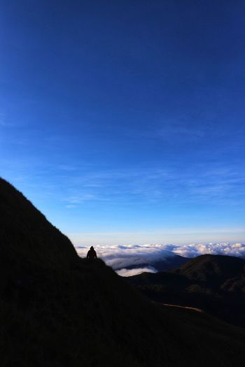 Scenic view of silhouette mountain against blue sky