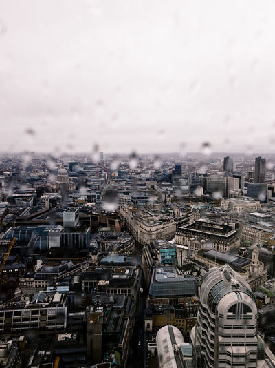 High angle view of buildings against sky with raindrops