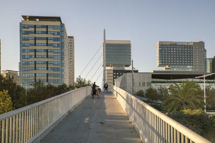 People on footbridge amidst buildings in city against clear sky