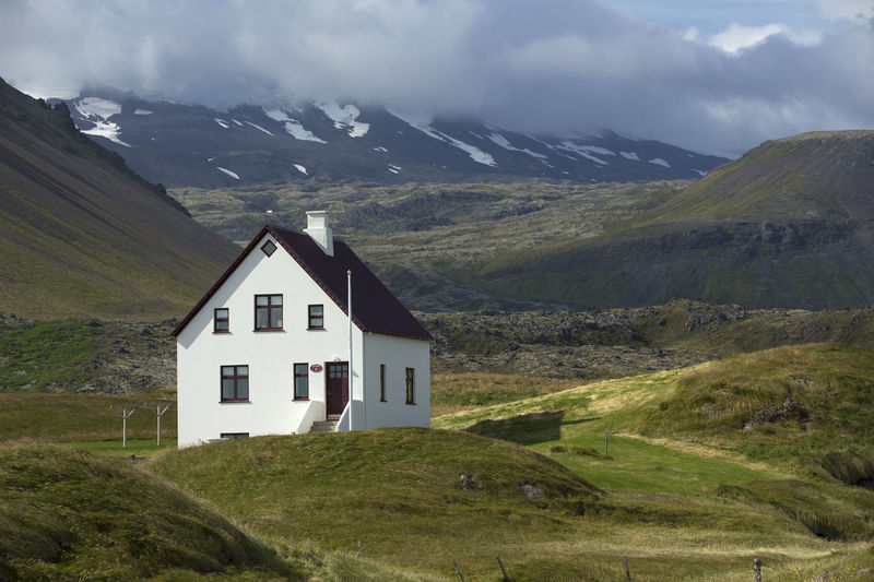Lonely house at the bottom of mountain, Iceland. Landscapes; Iceland; Nature; Scene; Nordic; Countries; Scenics; Mountain; Europe; Travel; Outdoors; House; North; Traditional; Exterior; Cottage; Culture; Building; Sea; Tranquil; City; Summer Mountain Building Architecture Beauty In Nature Built Structure Landscape Environment Day House No People Scenery Sky Grass Building Exterior Cloud - Sky Nature Green Outdoors Mountain Range Scenics - Nature