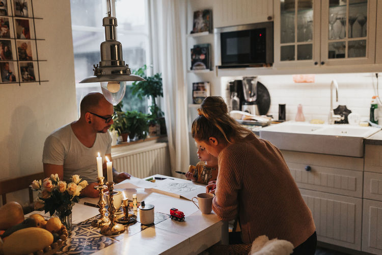 People sitting by table at home