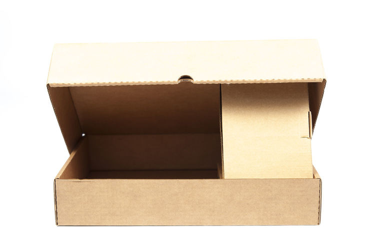 Close-up of open cardboard box over white background