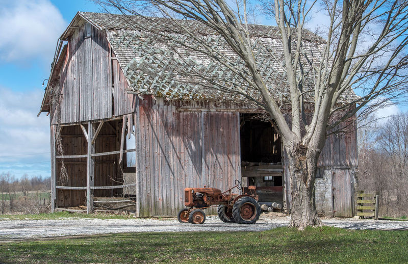 An antique collector tractor sits outside a rustic old barn in michigan usa