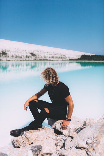 Blond curly guy is sitting on the stone around crystal clear water. Blond trendy hairstyle. Summer time, clear water, clear sky. Beauty In Nature Day Hair Hairstyle Healthy Lifestyle Leisure Activity Lifestyles Nature One Person Outdoors Real People Rock Rock - Object Scenics - Nature Solid Tranquil Scene Tranquility Water Wellbeing Women Young Adult Young Women