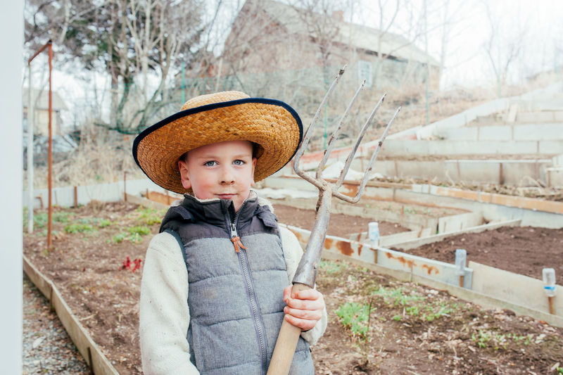 Cute light-skinned boy in a straw hat. activities for self-isolation in a country house.