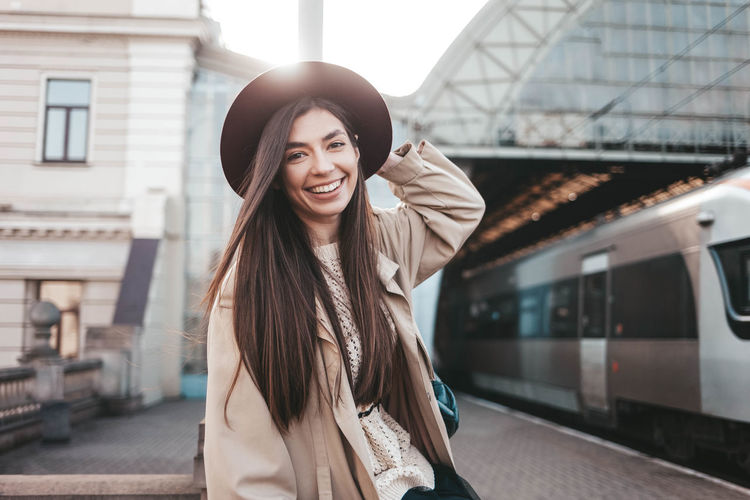 Portrait of beautiful young woman standing on railroad station platform