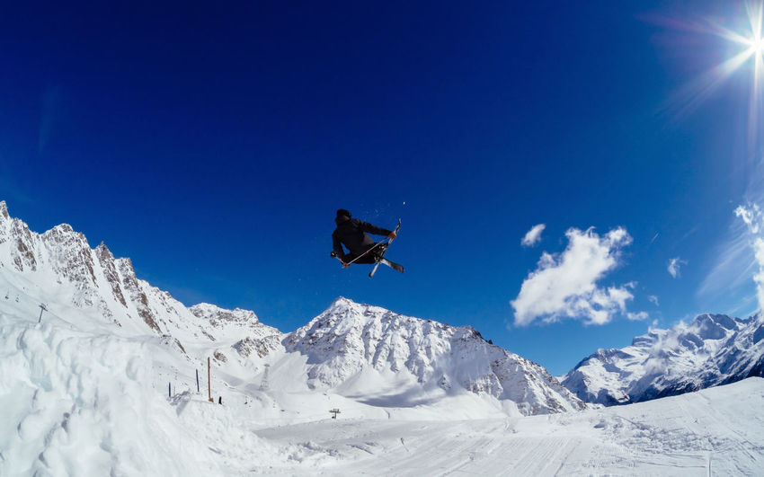 Low angle view of man jumping against snowcapped mountain