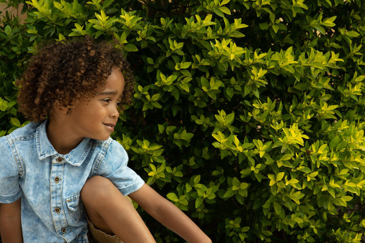 Portraits of nature Child Childhood One Person Looking Real People Casual Clothing Day Nature Leisure Activity Curly Hair Lifestyles Green Color Plant Looking Away Plant Part Leaf Hairstyle Focus On Foreground Outdoors Innocence Contemplation
