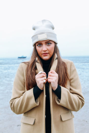 Portrait of beautiful woman in warm clothing standing against sea