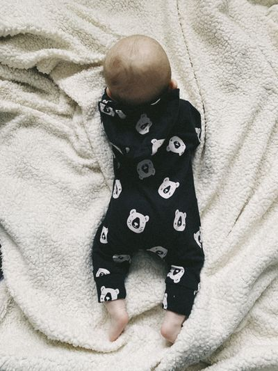 Indoors  One Person Real People High Angle View Childhood Child Lifestyles Baby Young Babyhood Bed Casual Clothing Furniture Leisure Activity Relaxation Toddler  Directly Above Innocence Back View Back Baby Clothes Newborn