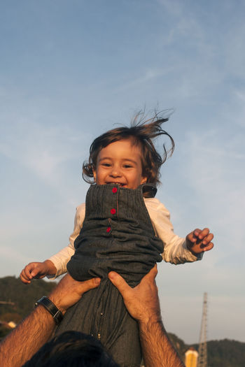 Cropped Hands Of Father Lifting Cheerful Daughter Against Sky