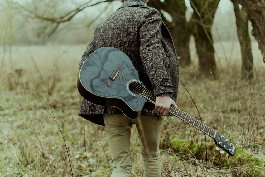 Arts Culture And Entertainment Day Field Guitar Music Musical Instrument Musician Nature One Person Outdoors Playing Plucking An Instrument Real People Standing Male Lifestyles Guy Guitarist Boy Lifestyle Young Adult
