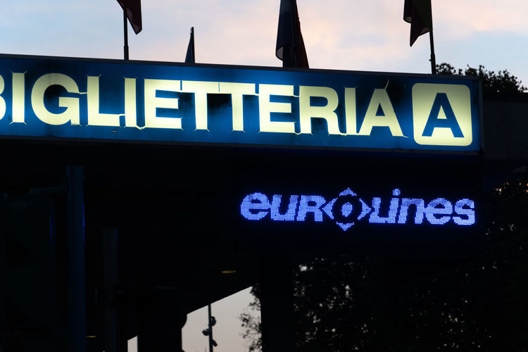 Blue signage of a Biglietteria, Italian for Ticket office, on a black background and EuroLines logo. The Belgian company operates a transnational network Eurolines Sale Blue Buy Communication Illuminated Information Information Sign No People Outdoors Retail  Sign Text Ticket Office Ticket Sale Ticket Seller Western Script