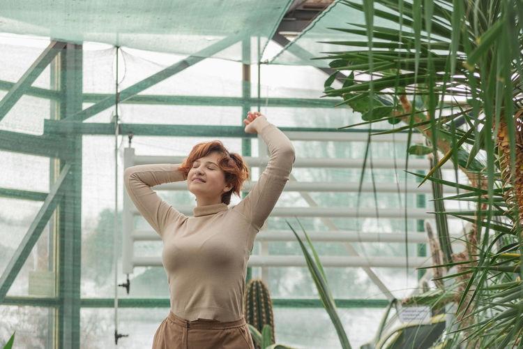 A beautiful plus size girl enjoying standing among the green plants