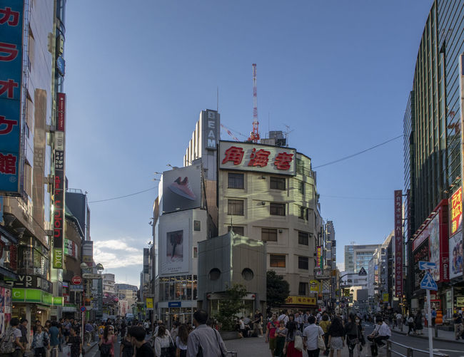 People on street amidst buildings in city against sky