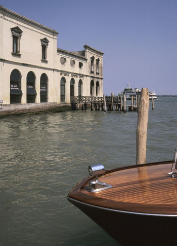 a glass factory and a motorboat in Murano island, Italy 35mm Film Analogue Photography Murano Architecture Building Exterior Built Structure Clear Sky Day Film Photography Glass Factory Italy Motorboat No People Travel Destinations Venetian Lagoon Waterfront