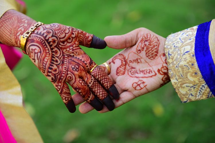 Cropped Hands Of Bride And Groom With Henna Tattoo