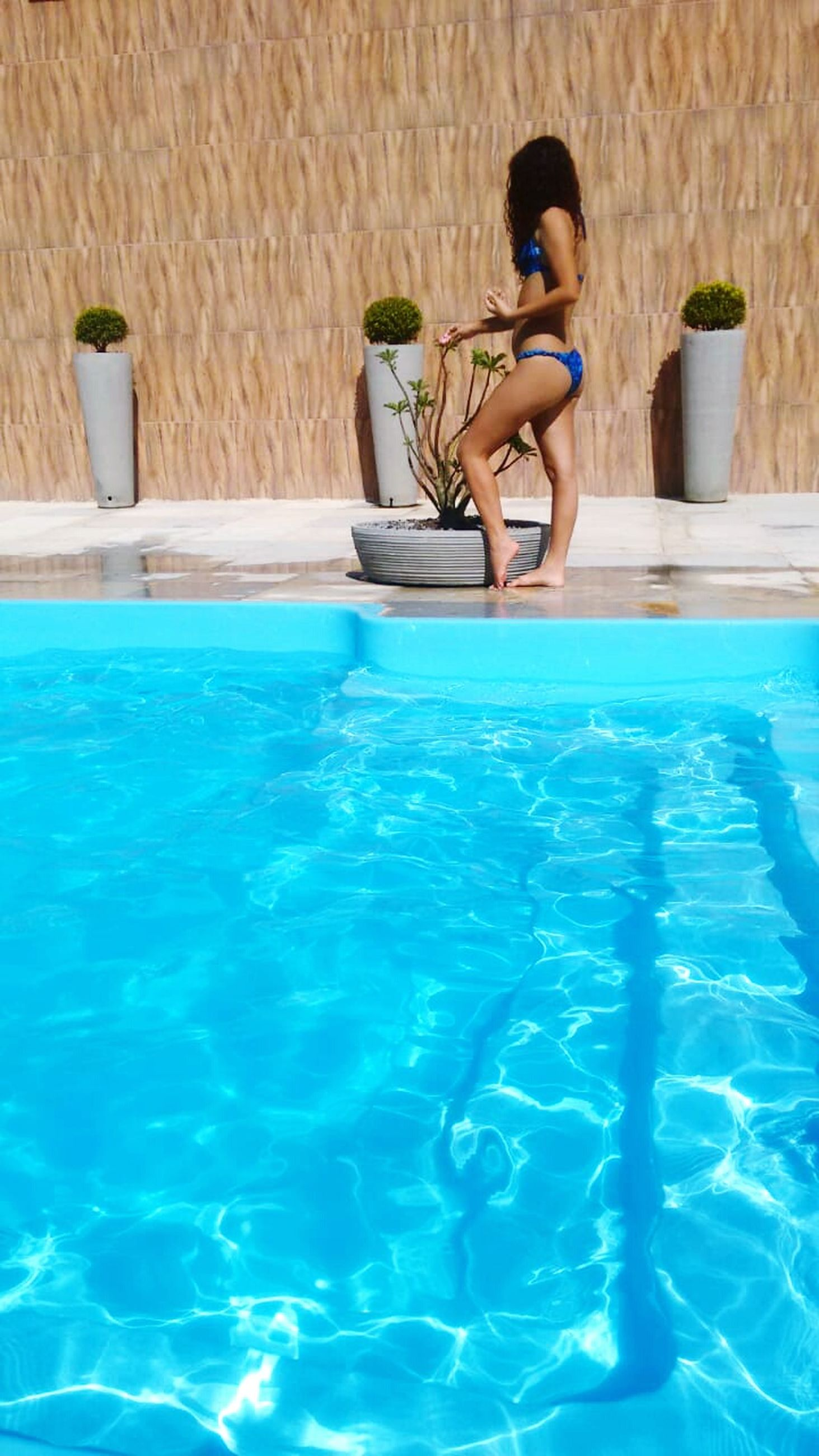 pool, swimming pool, one person, water, leisure activity, nature, sitting, full length, lifestyles, day, real people, waterfront, relaxation, women, adult, summer, young adult, blue, outdoors, turquoise colored, hairstyle