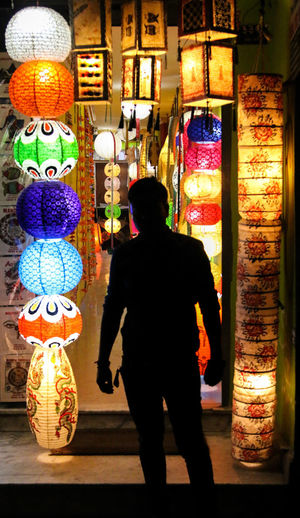 Rear view of man standing against illuminated store