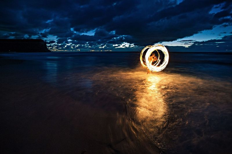 Person with illuminated wire wool on shore