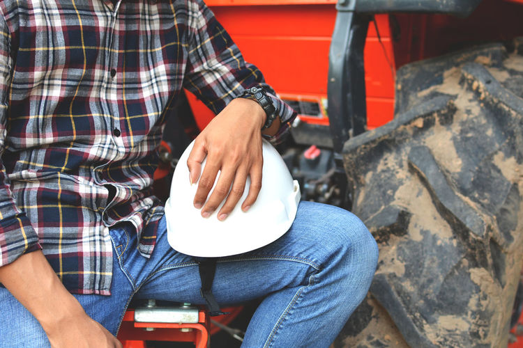 Midsection of worker holding hardhat while sitting outdoors