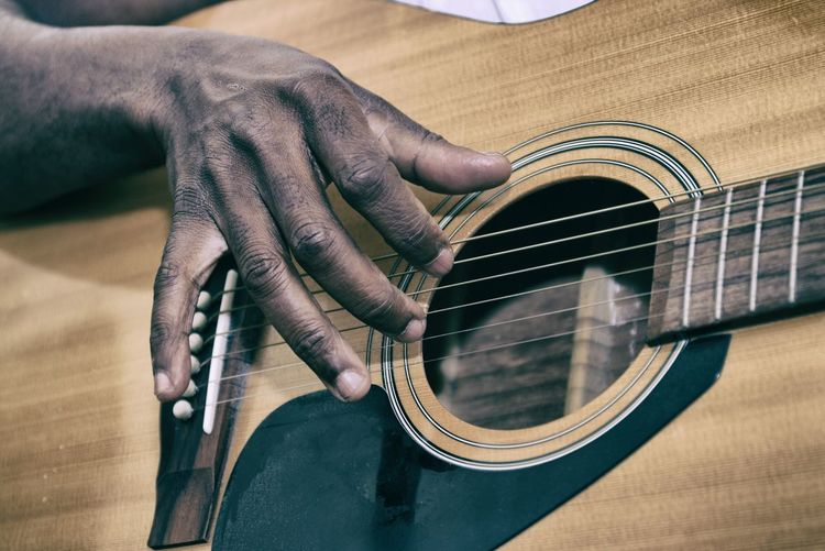 Cropped image of hand playing acoustic guitar