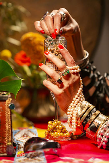 Gestures of a woman with jewelry, pearls, fruits and flowers. Abundance Wealth Celebration Art And Craft Mood Jewelry Gold Pearls Gesture Luxury Human Hand One Person Hand Human Body Part Focus On Foreground Ring Bracelet Indoors  Gold Colored Adult Belief Close-up Holding Fashion Selective Focus Nail Finger