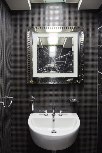 Sink and cracked mirror in bathroom