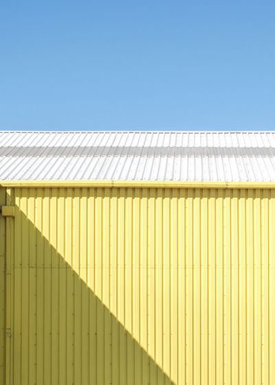 Yellow warehouse with shadow and blue sky