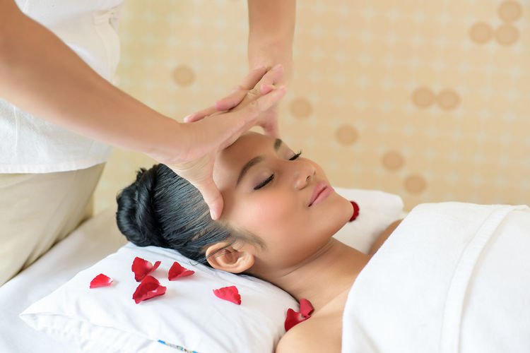 Midsection of masseuse giving head massage to young woman relaxing at spa