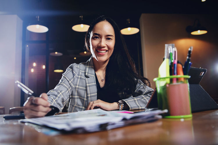 Portrait of smiling businesswoman writing on document while sitting in office