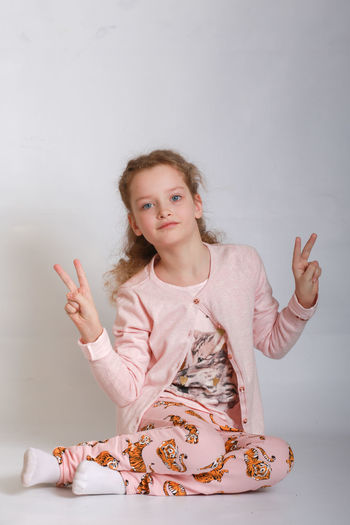 Portrait Of Girl Smiling While Sitting Against White Background