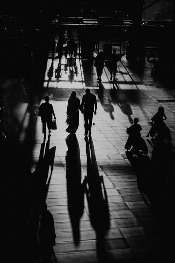 High angle view of silhouette people walking on road in city