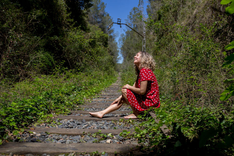 Woman sitting on plant by land