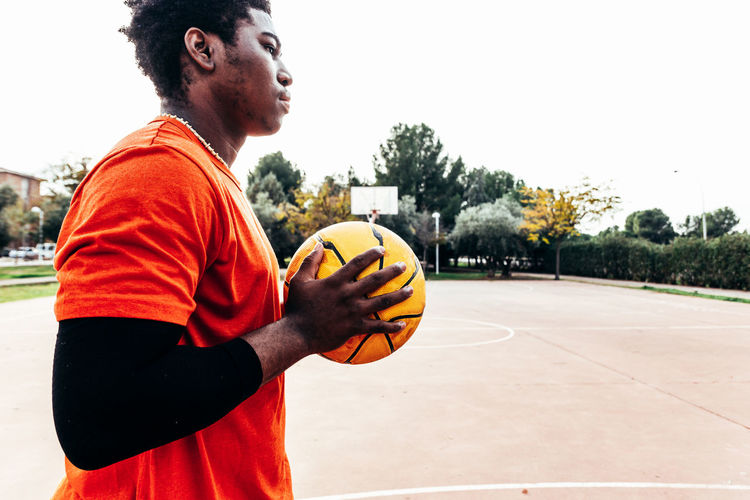 Young man holding basketball against hoop