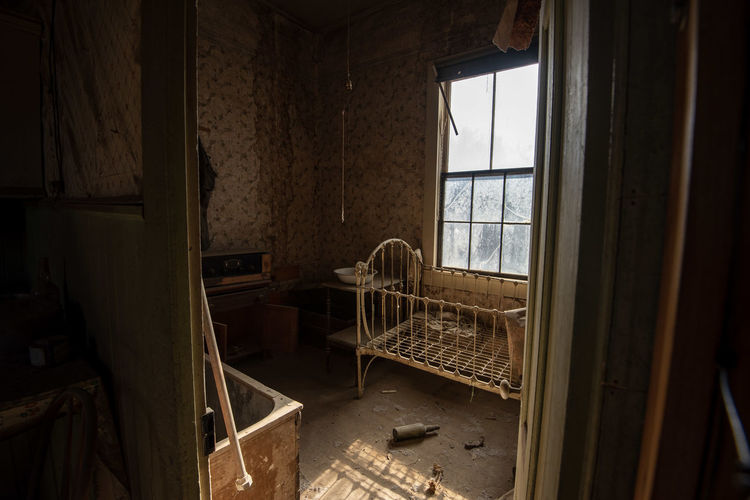 Interior of abandoned house in ghost town with baby cradle