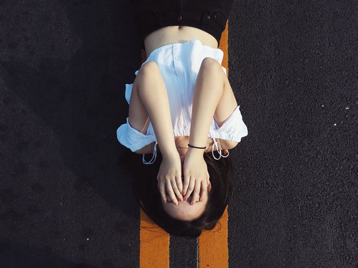 Directly above shot of woman covering face while lying on road