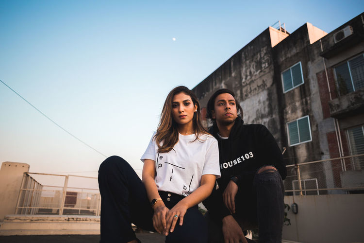 Young couple standing against building against clear sky