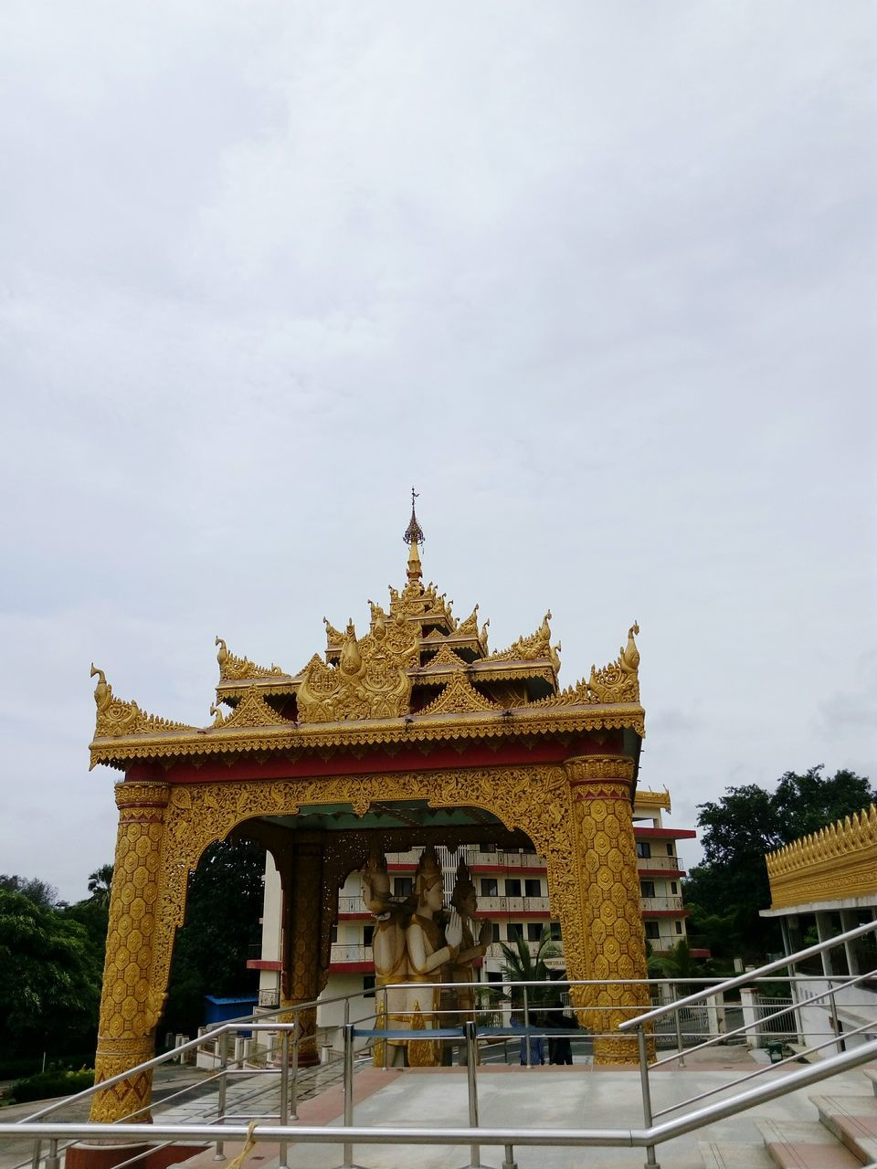 architecture, built structure, religion, building exterior, low angle view, travel destinations, gold colored, place of worship, sky, day, spirituality, sculpture, statue, outdoors, tree, no people, nature